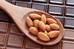 Amandelen in een houten lepel op chocoladeachtergrond Royalty-vrije Stock Afbeeldingen