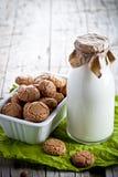 Amandelkoekjes in een kom en een fles melk Stock Afbeeldingen