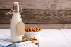 Amandelmelk in fles met etiket en amandelnoten op rustieke houten lijst Concept van lactose het vrije zuivelproducten stock fotografie