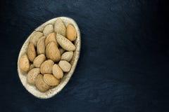 Amandes avec la coquille de noix dans le plat naturel de feuille de banane d'Eco sur la surface en pierre noire de fond avec l'es photo libre de droits