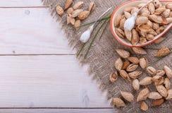 Amandes dans leurs peaux et peele dans la cuvette brune sur le fond en bois Image libre de droits