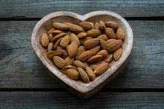 Amandes dans un plat en forme de coeur en bois photo stock