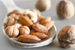 Amandes, noisettes, noix, noix de cajou dans une cuillère en bois, et trois noix entières sur Gray Background Casse-cro?te organi image libre de droits