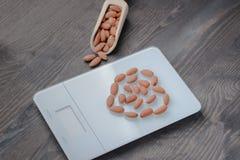 Amandes Nuts sur les échelles et le fond en bois Image libre de droits