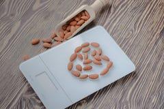 Amandes Nuts sur les échelles et le fond en bois Photos libres de droits