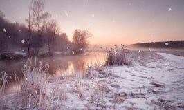 Amanecer brumoso del invierno en el río Copos de nieve, nevadas Wint soleado Fotos de archivo libres de regalías