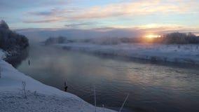 Amanecer de la mañana en el río en una evaporación fuerte de la helada del agua en frío punzante metrajes