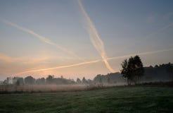 Amanecer del otoño sobre prados y el cielo con los rastros de aviones imagen de archivo