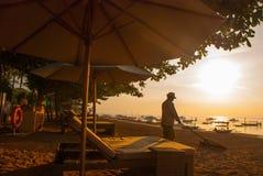 Amanecer hermoso en la playa en Sanur El trabajador limpia la playa Fotos de archivo
