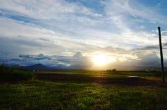 Amanecer que se rompe sobre campo de la tierra de cultivo foto de archivo