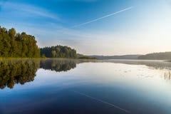 Amanezca en el lago del bosque debajo del cielo azul Imagen de archivo libre de regalías