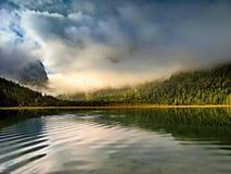 Amanezca en un lago de la montaña con las nubes y la niebla Fotos de archivo