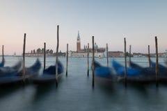 Amanezca en Venecia con las góndolas y los posts del amarre Imagen de archivo libre de regalías