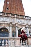 Amanhecer em Veneza, uma máscara senta-se para baixo sob a torre Imagem de Stock