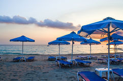 Amanhecer vazio da praia Parasóis e sunbeds fotos de stock royalty free