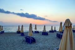 Amanhecer vazio da praia Parasóis fechados e sunbeds empilhados Foto de Stock