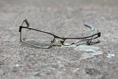 Łamani eyeglasses na betonie Fotografia Royalty Free