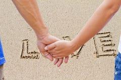 Amant écrit dans le sable sur la plage Photographie stock libre de droits