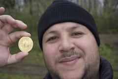 amant de bitcoin avec une pièce d'or dans votre main, mineur drôle avec BTC près du visage Photo stock