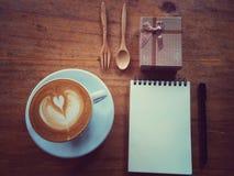 amant de café avec le livre de carnet et de cadeau Photographie stock libre de droits