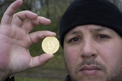 Amant fol de bitcoin avec une pièce d'or dans votre main, mineur drôle avec BTC près du visage Photo stock