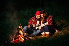 Amantes alrededor de la hoguera en la noche Fotos de archivo libres de regalías