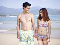 Amantes asiáticos jovenes que caminan en la playa Imagen de archivo