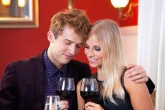 Amantes bastante dulces que sostienen el vidrio de vinos Fotografía de archivo libre de regalías