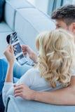 Amantes caucasianos no sofá que olha imagens agradáveis Imagem de Stock
