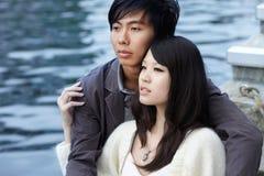 Amantes chineses novos que abraçam pelo rio Imagem de Stock Royalty Free