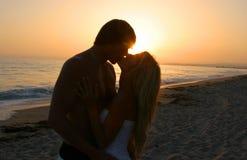 Amantes da silhueta que beijam na praia do tne Fotos de Stock