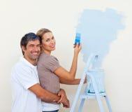Amantes de sorriso que pintam um quarto Imagem de Stock