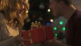 Amantes felices que intercambian los regalos en la Navidad, expresando alegría y besarse infantiles almacen de metraje de vídeo