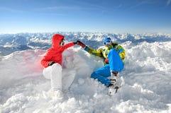 Amantes felizes que prendem as mãos na parte superior de um slo do esqui imagens de stock royalty free