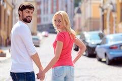 Amantes jovenes alegres que disfrutan del paseo a través de ciudad Foto de archivo libre de regalías