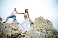 Amantes jovenes hombre y mujer que caminan en las montañas Imagen de archivo libre de regalías