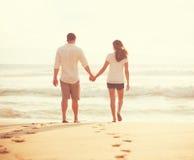 Amantes jovenes que caminan abajo de la playa en la puesta del sol Imágenes de archivo libres de regalías