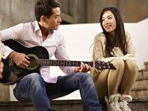 Amantes jovenes que tocan la guitarra y que cantan Imagenes de archivo