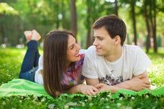 Amantes jovenes sonrientes hacia fuera en la mentira del parque Imágenes de archivo libres de regalías