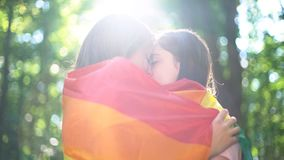 Amantes lésbicas envolvidos no beijo da bandeira do arco-íris, na ternura e no amor, direitos do lgbt foto de stock royalty free