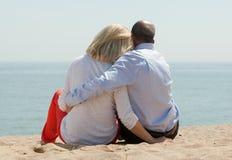 Amantes maduros que se sientan en la playa Imagenes de archivo