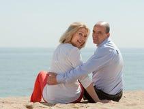 Amantes maduros que se sientan en la playa Imagen de archivo