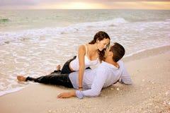 Amantes mojados en la playa en la puesta del sol Foto de archivo libre de regalías