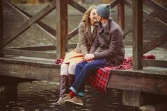 Amantes mujer y hombre que se sientan cerca del lago foto de archivo libre de regalías