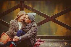 Amantes mujer y hombre que se sientan cerca del lago Fotografía de archivo