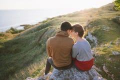 Amantes novos, pares, por do sol pelo mar, as montanhas Imagens de Stock Royalty Free