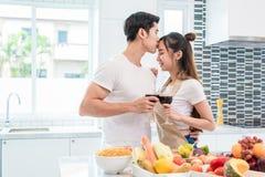 Amantes ou pares asiáticos que beijam a testa e que bebem o vinho no ki fotografia de stock royalty free