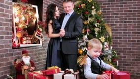 Amantes, padres felices que bailan cerca de un niño que juega la víspera de la Navidad cerca del árbol de navidad, familia feliz almacen de metraje de vídeo