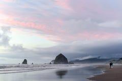 Amantes que admiran la roca del pajar en la puesta del sol Imagen de archivo libre de regalías