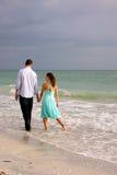Amantes que andam em conjunto ao longo da praia no flo Fotos de Stock Royalty Free